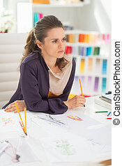 Thoughtful fashion designer in office
