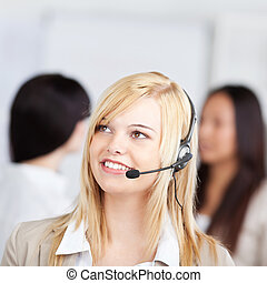 Thoughtful female customer service representative wearing headset with female coworkers in background in office
