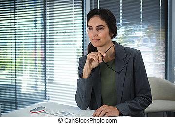 Thoughtful female executive sitting at desk