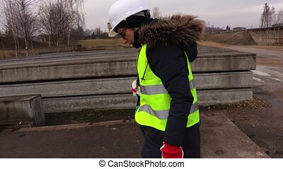 Thoughtful Female inspector checking concrete blocks