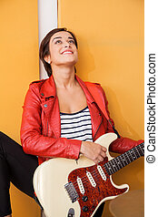Thoughtful Female Singer With Guitar