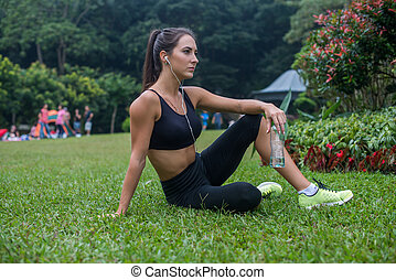 Thoughtful fitness girl sitting on grass in park resting after exercising or running, listening to music and holding a bottle of water