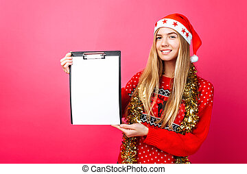 Thoughtful girl in a red sweater and Santa hat, holding a tablet with a clean sheet and pointing a finger at him, planning the coming New year on a red background.