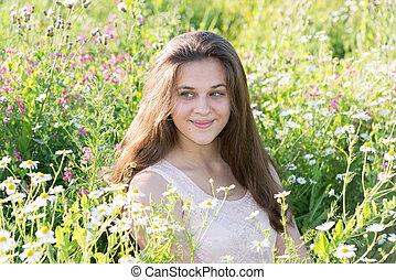 Thoughtful girl in summer dress in a meadow