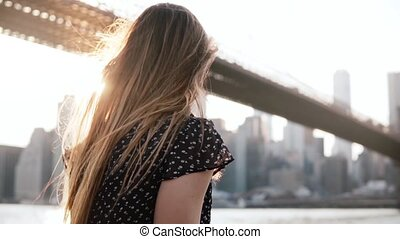 Thoughtful girl in sunglasses with amazing hair blowing in the wind enjoying New York sunset scenic view slow motion.
