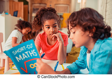 Thoughtful girl learning math with her classmate