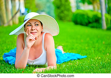 thoughtful girl lies on a green lawn in a white hat