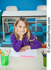 Thoughtful Girl Sitting With Hand On Chin In Classroom