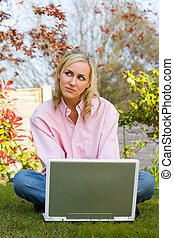Thoughtful Girl Young Woman Using a Laptop Computer in Her Garden at Home
