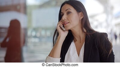 Thoughtful gorgeous woman chatting on a mobile