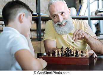 Thoughtful granddad teaching kid chess game