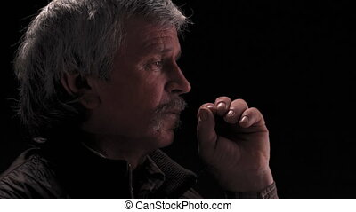 Thoughtful grey haired senior man looking side ways turn head on camera and smile with camera slide wearing jacket in semi lit light studio isolated on black background. Prores 422.