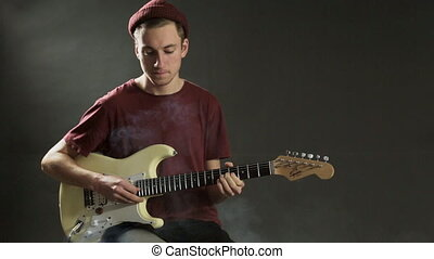 Thoughtful guitarist playing guitar in dark studio in smoke