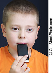 Thoughtful kid in orange with cellphone
