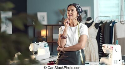 Thoughtful attractive lady leaning on table with sewing tools and dreaming about future clothing collection. Female designer with dark hair looking for new ideas and inspiration in studio.