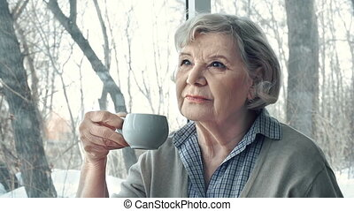 Thoughtful Lady - Side view of senior lady having tea and...