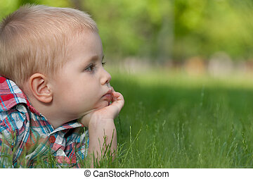 Thoughtful little boy on the grass