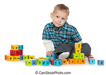 Thoughtful little boy with blocks