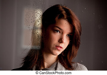 Thoughtful lonely young girl at the window - Sad pensive...