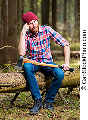 thoughtful lumberjack in a hat and shirt with an ax sits on a log in the woods