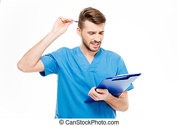Thoughtful male doctor standing with clipboard
