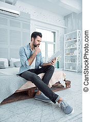 Thoughtful male person working at home