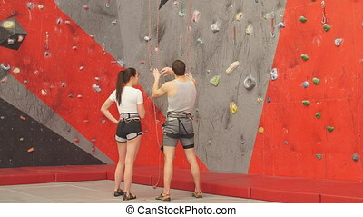 Thoughtful man and woman analyzing the route of climbing at...