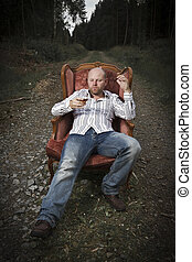 Thoughtful Man Drinking Cognac in a Vintage Chair