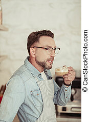 Thoughtful man going to drink his coffee.