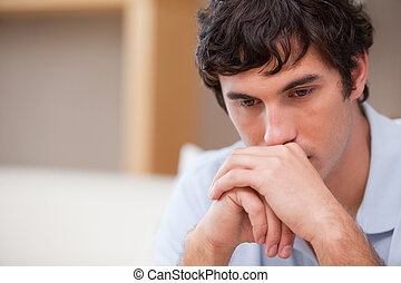 Thoughtful man in the living room - Thoughtful young man in...
