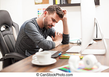 Thoughtful man leaning on his desk at work