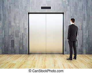 Thinking man looking at elevator  Thinking young businessman looking