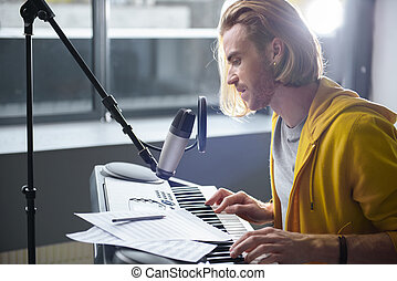 Thoughtful man playing electric piano