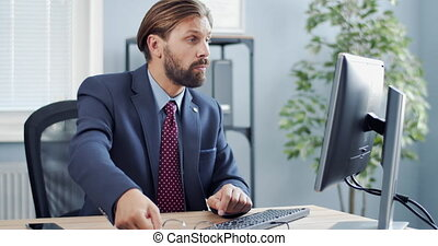 Thoughtful man sitting at workplace and using computer - ...