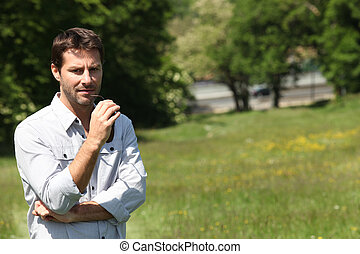 Thoughtful man standing in  a park