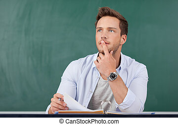 Thoughtful Man With Folder In Front Of Chalkboard