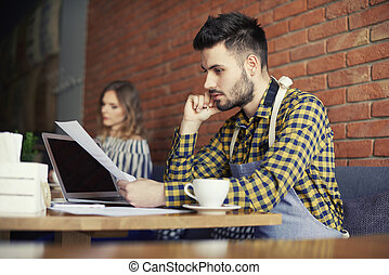 Thoughtful man with hand on chin over paperwork