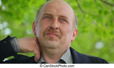 thoughtful man with moustache stands under tree