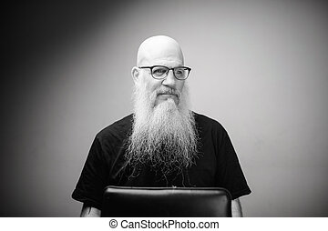 Thoughtful mature bald man with long gray beard wearing eyeglasses in black and white