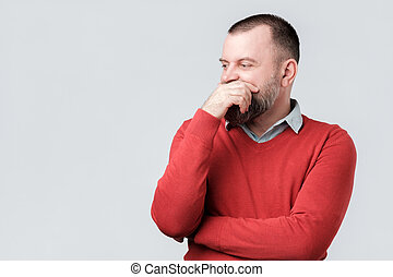mature man in red sweater looking aside thinking and rubbing his chin