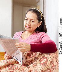 thoughtful mature woman with newspaper