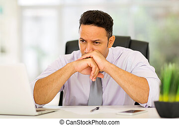 thoughtful middle aged businessman in office
