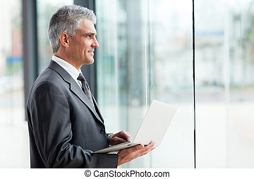 thoughtful middle aged businessman with laptop