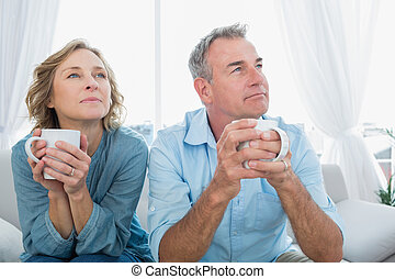 Thoughtful middle aged couple sitting on the couch having...