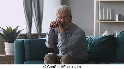 Thoughtful tired middle aged man sitting on couch relying on walking stick, feeling stressed. Depressed mature grandfather thinking of geriatric health problems disease, suffering from loneliness.