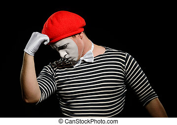Thoughtful mime, isolated on black. Dressed in black and white striped t-shirt