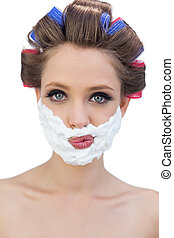 Thoughtful model in hair curlers posing with shaving foam
