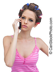 Thoughtful model in hair rollers on the phone