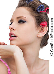Thoughtful model with hair curlers