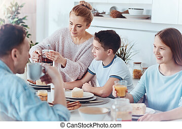 Thoughtful mother taking care of family during breakfast